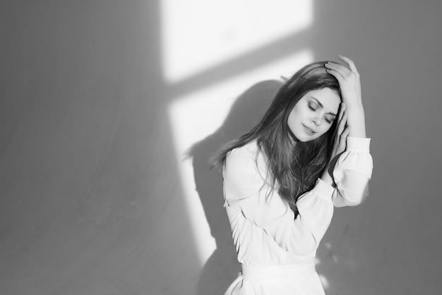 Hübsche frau im kleid schwarz-weiß-foto posiert studio