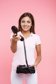 Hübsche frau im lässigen outfit macht telefonanrufe und hält empfänger