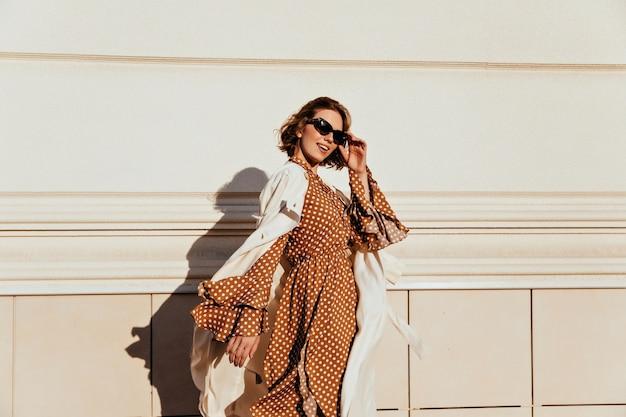 Hübsche frau im langen braunen kleid, das sonnigen tag genießt. liebenswertes weißes mädchen in der retro-kleidung, die die straße entlang geht.