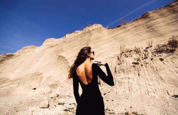 Hübsche frau im langen schwarzen kleidergehen im freien