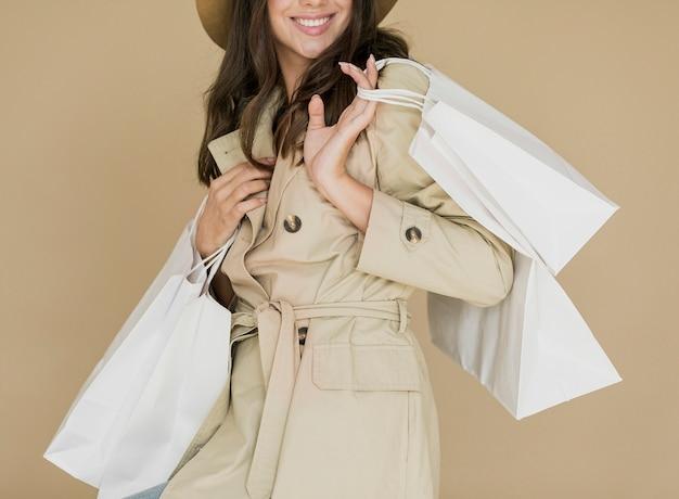 Hübsche frau im mantel und im braunen hut mit einkaufsnetzen