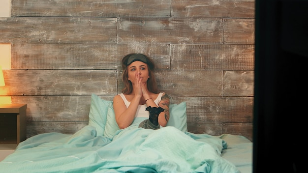Hübsche frau im pyjama hat nachts angst vor horrorfilm im fernsehen