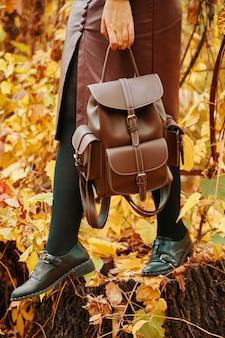 Hübsche frau im rock und mit rucksack herbstspaziergang im park herbstlaub im hintergrund nat...