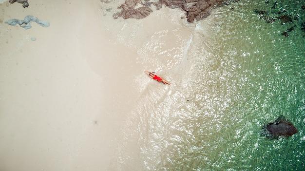 Hübsche frau im roten bikini-badeanzug genießt meerwasser, braunen sand. vogelperspektive von einer drohne genommen. luftbild