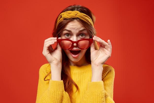Hübsche frau im roten brillenstirnband-hipster-mode posiert