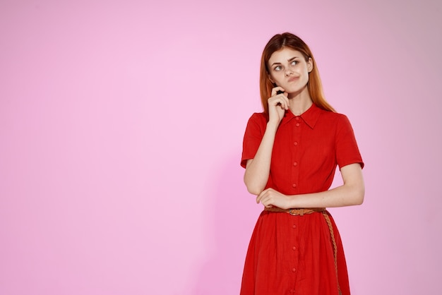 Hübsche frau im roten kleid, das modeluxus aufwirft