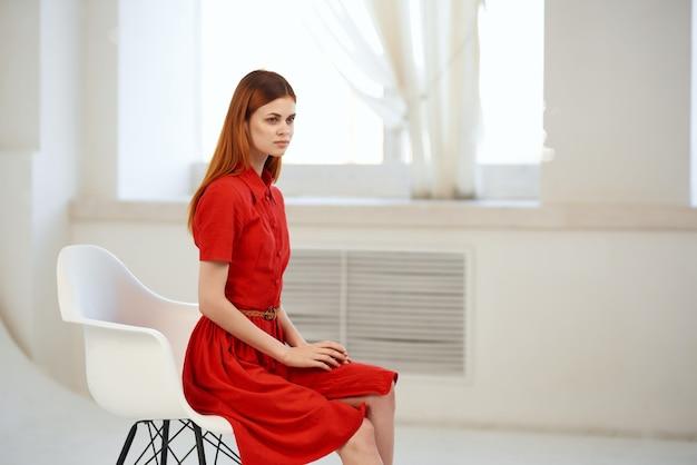 Hübsche frau im roten kleid, die auf einem stuhlluxus aufwirft. foto in hoher qualität