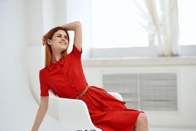 Hübsche frau im roten kleid, die auf einem stuhlluxus aufwirft