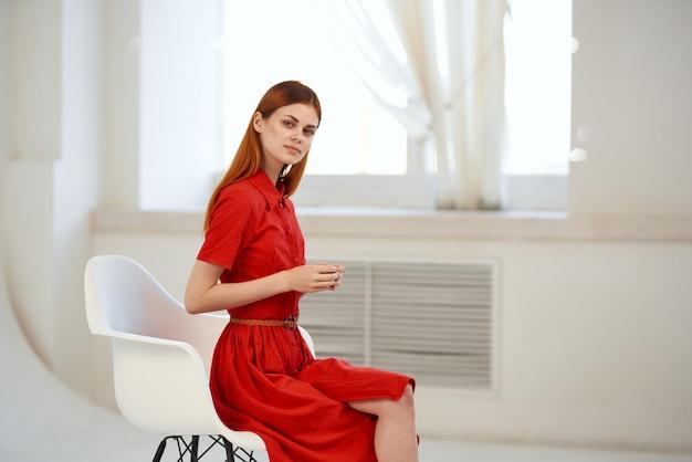 Hübsche frau im roten kleid, die nahe dem eleganten stil des fensters sitzt