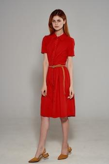 Hübsche frau im roten kleid handgesten luxusstudio