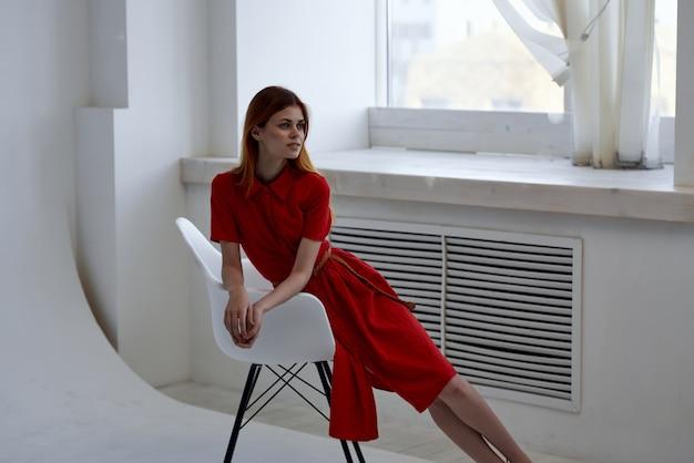 Hübsche frau im roten kleid posiert auf einem stuhl im eleganten stil