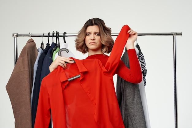 Hübsche frau im roten kleid shopaholic, die kleidung kauft, die im geschäft lokalisierter hintergrund einkauft