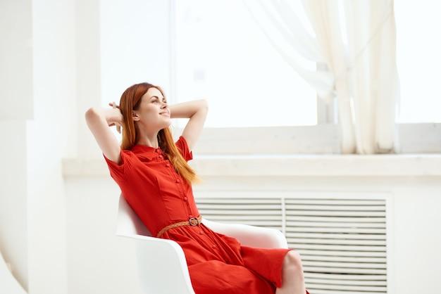 Hübsche frau im roten kleid sitzt auf einem stuhl mode