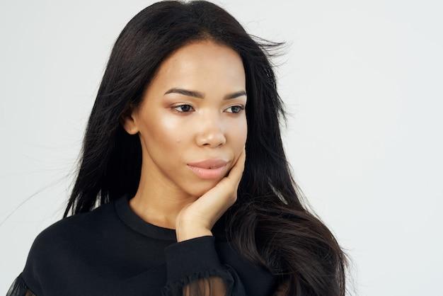 Hübsche frau im schwarzen hemd mit langen haaren kosmetik gesicht nahaufnahme