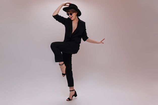 Hübsche frau im schwarzen outfit und im hut bewegt sich auf weißem hintergrund. charmante dame in dunkler jacke und hose tanzt und springt isoliert auf