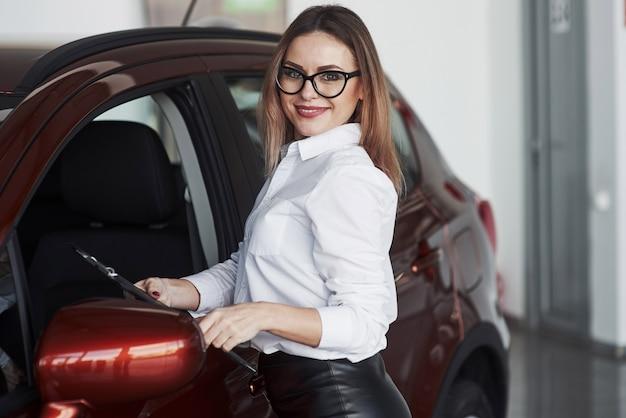 Hübsche frau im schwarzen rock, der nahe nagelneues auto im autosalon aufwirft