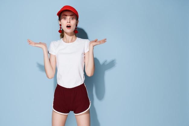 Hübsche frau im sommermodesportart des weißen t-shirts mit roter kappe
