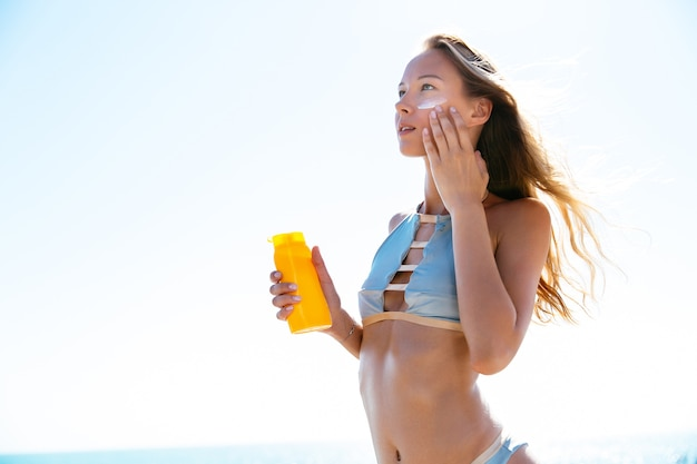 Hübsche frau im stilvollen badeanzug, der bräunungscreme auf ihr gesicht setzt