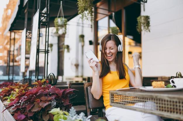 Hübsche frau im straßencafé im freien, die am tisch sitzt, musik über kopfhörer hört, das handy benutzt, sich in der freizeit im restaurant entspannt?