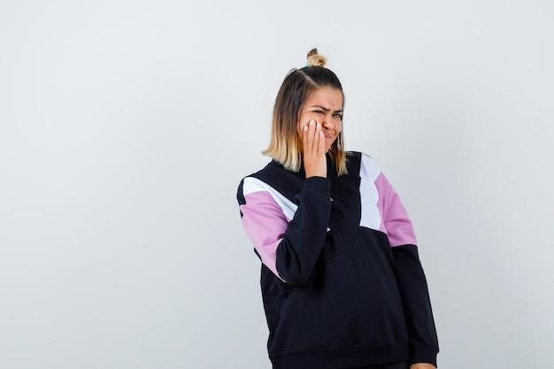 Hübsche frau im sweatshirt, die unter zahnschmerzen leidet und schmerzhaft aussieht