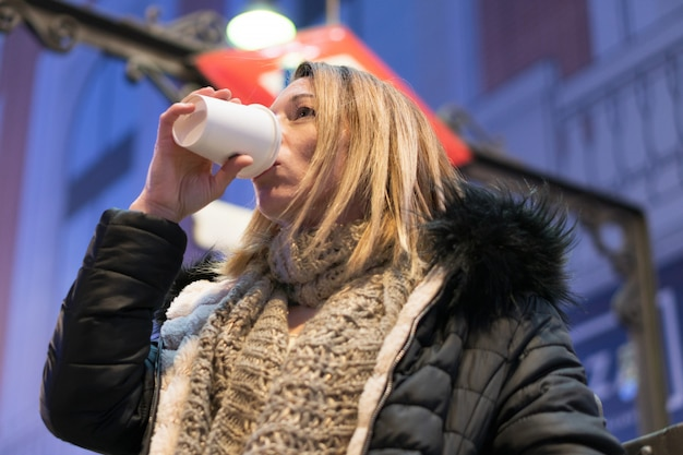 Hübsche frau im trinkenden kaffee der nachtstadt. stadt beleuchtet hintergrund.
