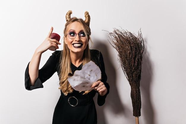 Hübsche frau im vampirkostüm, die spaß in halloween hat. frohe junge hexe, die gesichter auf weißer wand macht.