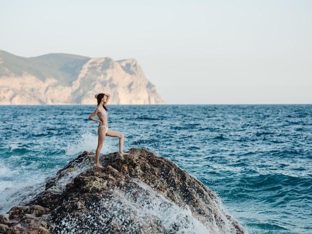 Hübsche frau im weißen bikinistrand, der felsensommer aufwirft