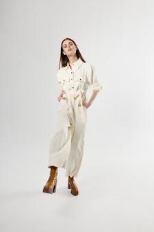 Hübsche frau im weißen ganzkörperanzug isolierte modeschuhe