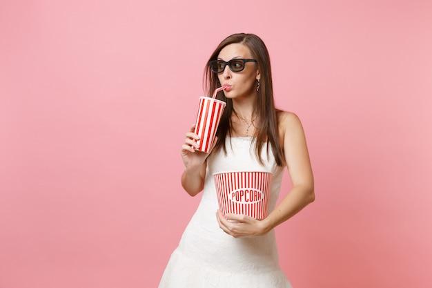 Hübsche frau im weißen kleid, 3d-brille, die filmfilm sieht, eimer popcorn, plastikbecher soda oder cola hält