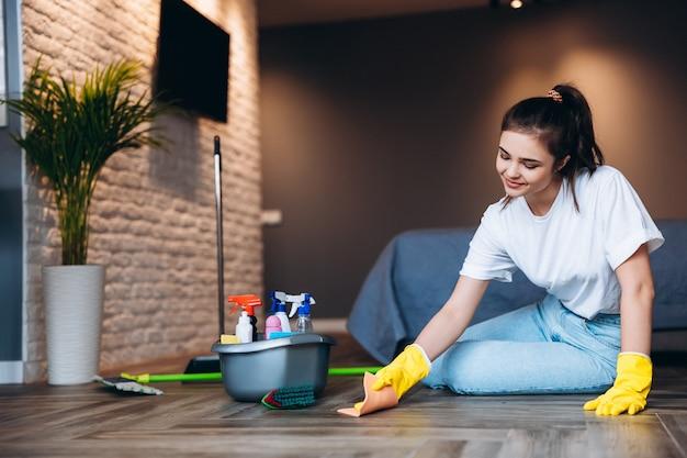 Hübsche frau im weißen t-shirt mit dunkler haarreinigung in gelben gummihandschuhen für handschutz und eimer mit reinigungsmitteln zu hause