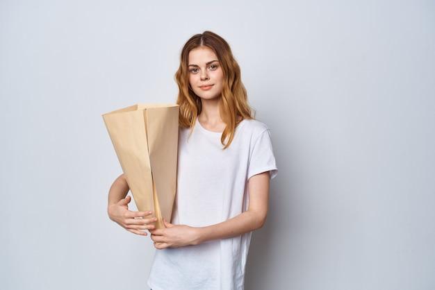 Hübsche frau im weißen t-shirt mit einkaufstasche in den händen