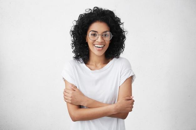 Hübsche frau im weißen t-shirt und in den runden brillen, die schüchtern fühlen