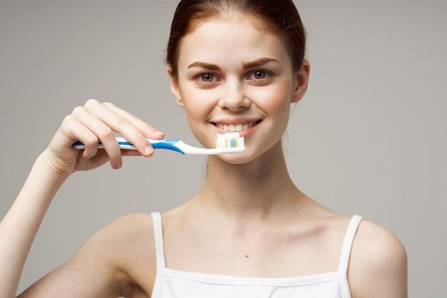 Hübsche frau im weißen t-shirt zahnhygiene gesundheitsstudio lebensstil. foto in hoher qualität