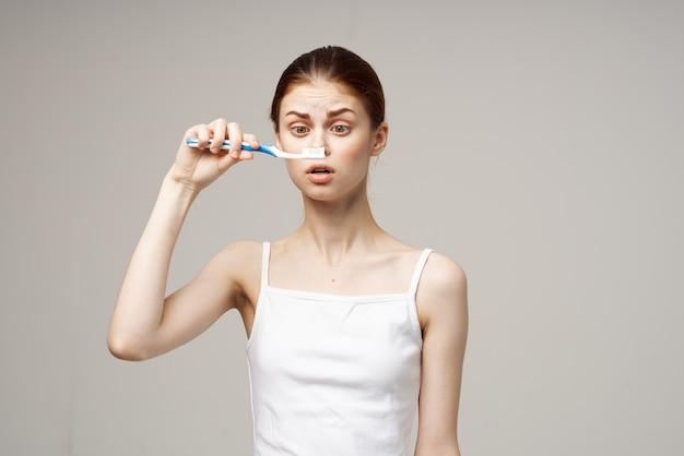 Hübsche frau im weißen t-shirt zahnhygiene gesundheitswesen heller hintergrund