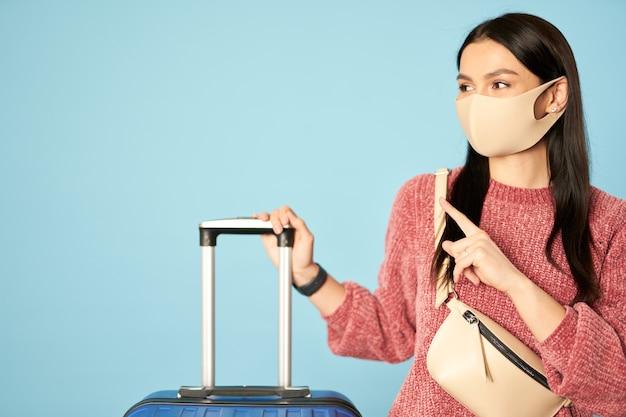 Hübsche frau in antivirus-gesichtsmaske, die die reise genießt