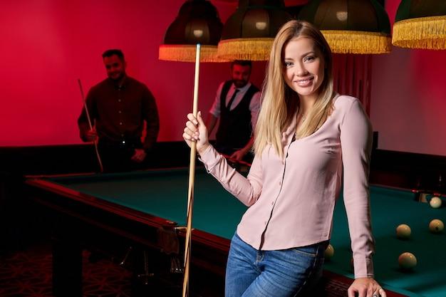 Hübsche frau in der bar neben billardtischpool, leute, die snooker spielen
