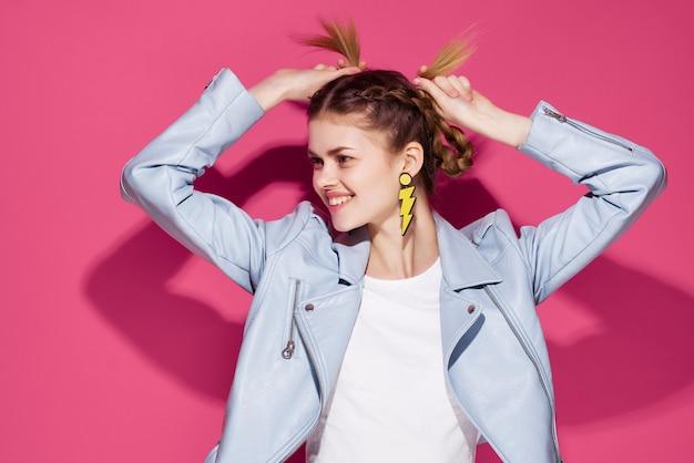 Hübsche frau in der blauen jacke mode zöpfe hellen make-up dekoration rosa hintergrund