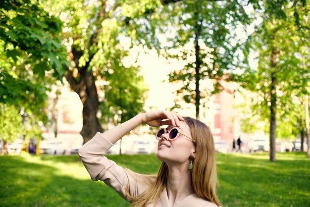 Hübsche frau in der dunklen runden brille und in den sommerferien im park.