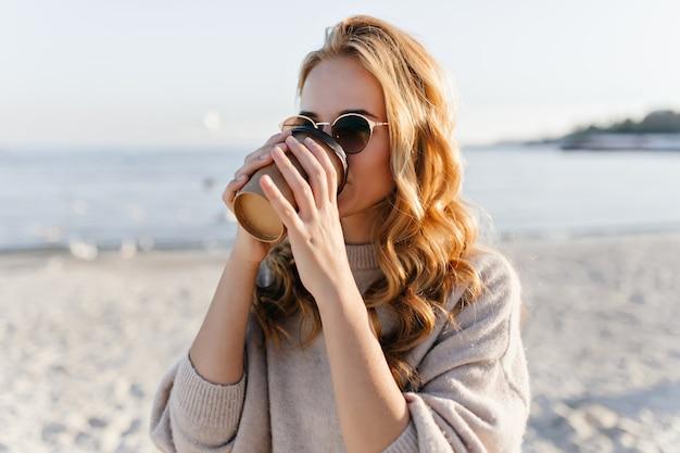 Hübsche frau in der eleganten sonnenbrille, die an der seeküste ruht. außenporträt des verträumten weiblichen modells, das im herbsttag kühlt.