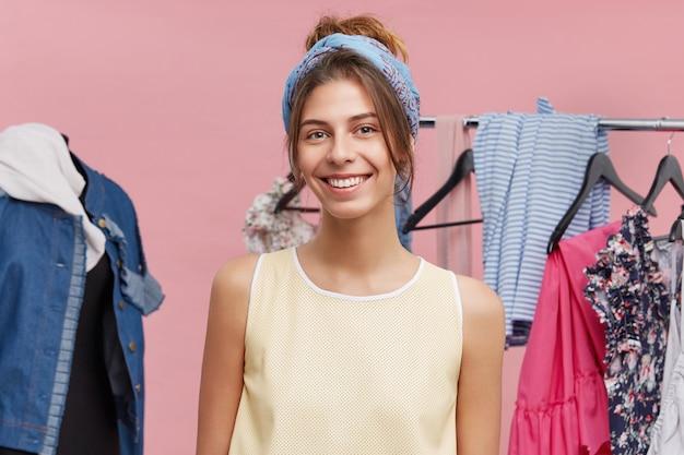 Hübsche frau in der guten laune, die frühjahrsputz in ihrem kleiderschrank tut, mit kleiderbügeln am gestell stehend, mit glücklichem freudigem lächeln schauend.