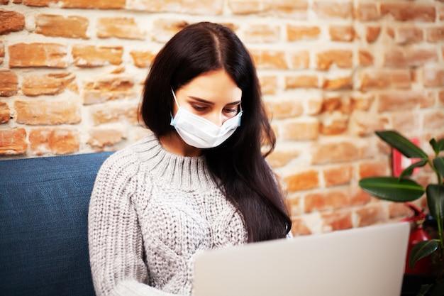 Hübsche frau in der maske auf ihrem gesicht, die zu hause während der pandemie am laptop arbeitet