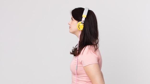 Hübsche frau in der profilansicht, die mit kopfhörern musik hört, sich vorstellt oder träumt