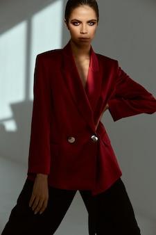 Hübsche frau in der roten blazer-studiomode beschnittene ansicht. hochwertiges foto