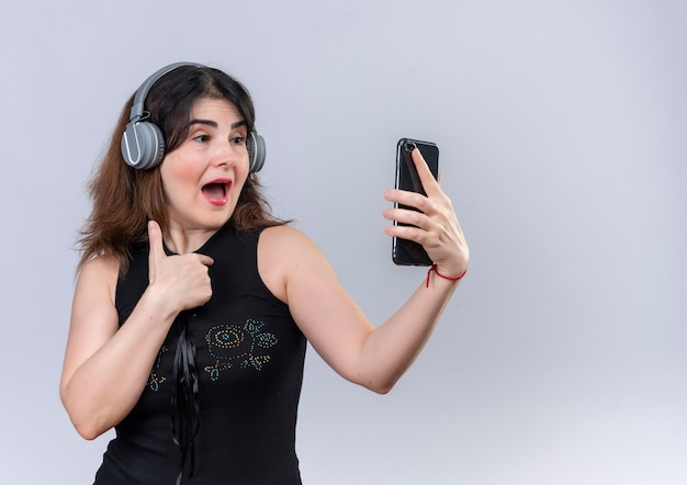Hübsche frau in der schwarzen bluse, die musik mit kopfhörern hört, die mit telefon slefie machen