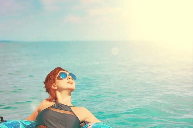 Hübsche frau in der sonnenbrille entspannen sich auf aufblasbarem ring im ozean