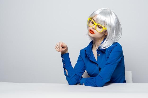 Hübsche frau in der weißen perücke gestikulierend mit der gelben brille der handroten lippen