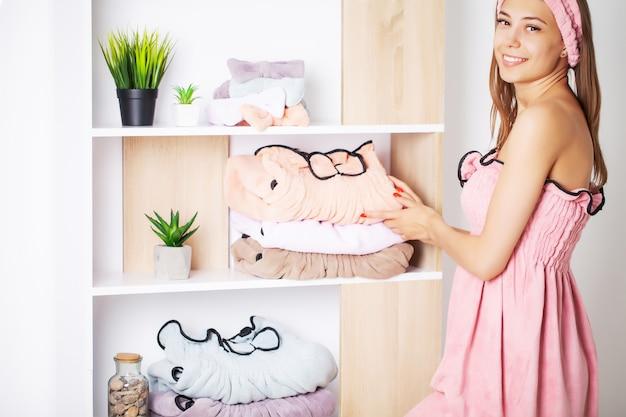 Hübsche frau in einem handtuchkleid mit perfekter haut nach spa-behandlungen zu hause