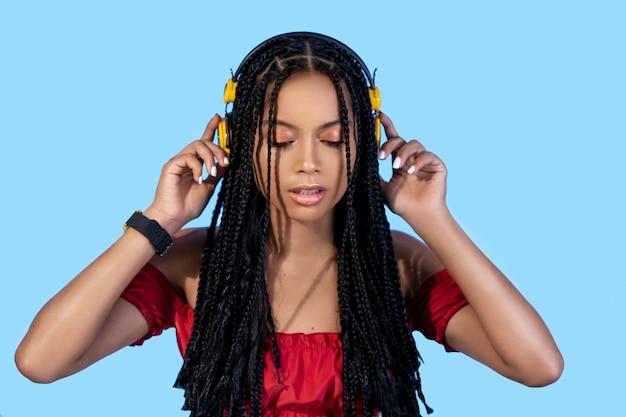 Hübsche frau in einem roten kleid, das in den gelben kopfhörern und in der armbanduhr auf blau aufwirft. der musikgeschmack.