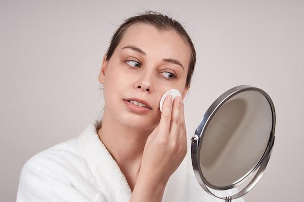 Hübsche frau in einem weißen gewand reinigt ihr gesicht mit einem wattepad und schaut in den spiegel. lichtwand.