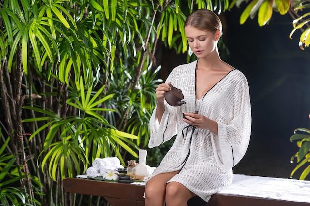 Hübsche frau in einem weißen kittel gießt tee ein. teezeremonie, thai-massage